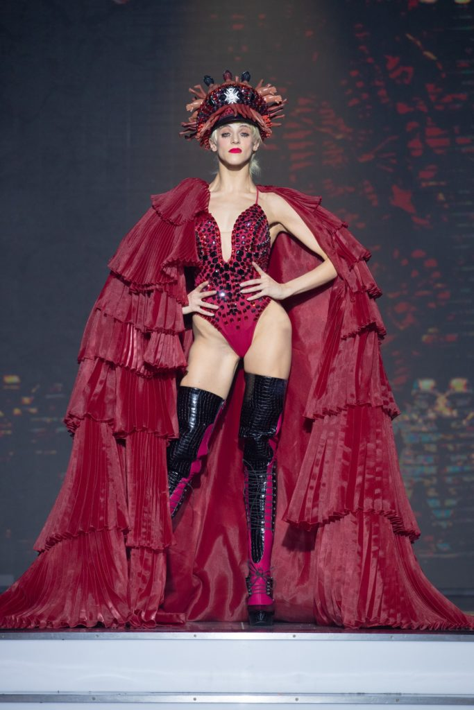 a model wearing red cap and body crystal by on aura tout vu couture spring summer 2020