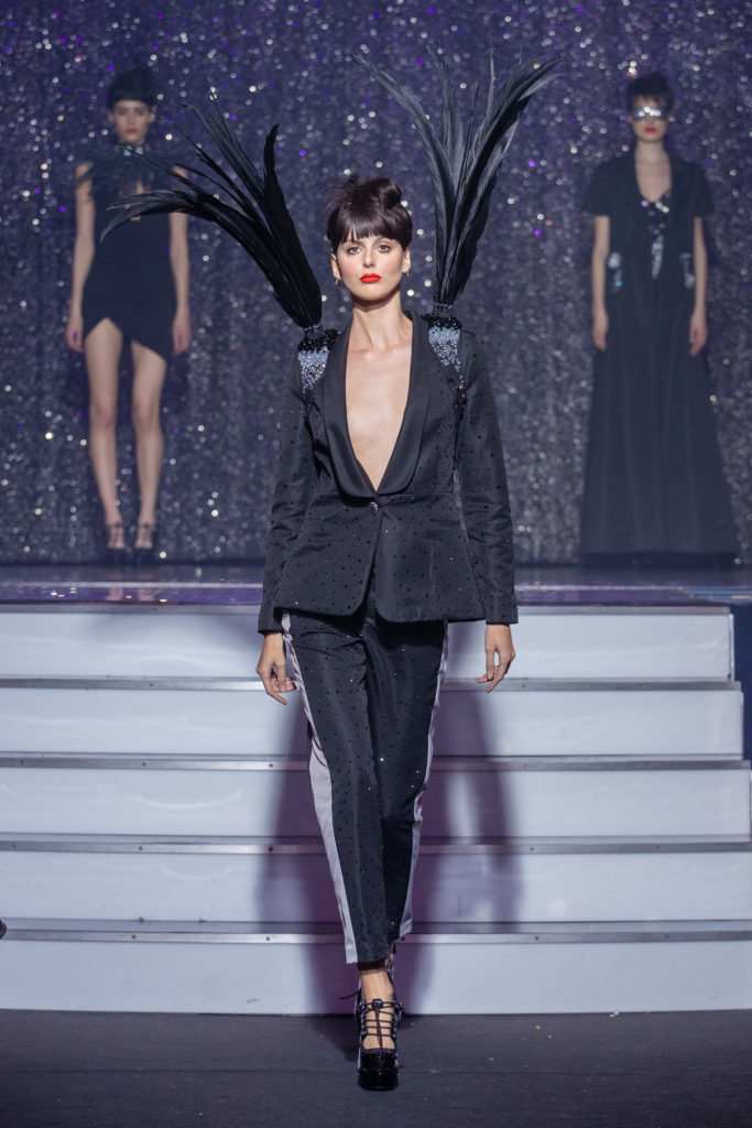 a model wearing  black silk  outfit  crystal  harness feathers  by on aura tout vu haute couture spring summer 2020