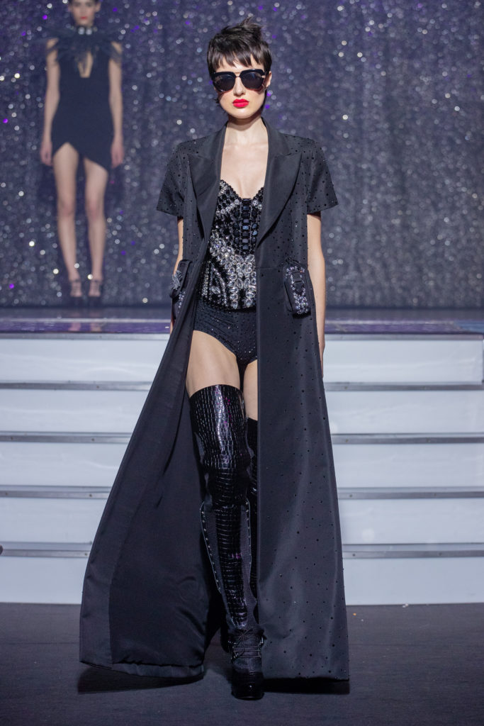 a model wearing  blacksilk  coat crystal  corset sunglases  by on aura tout vu haute couture spring summer 2020