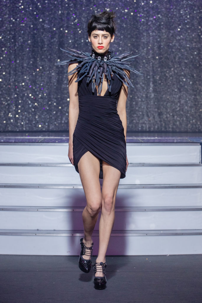 a model wearing  black tulle outfit  crystal and puppet necklace  by on aura tout vu haute couture spring summer 2020