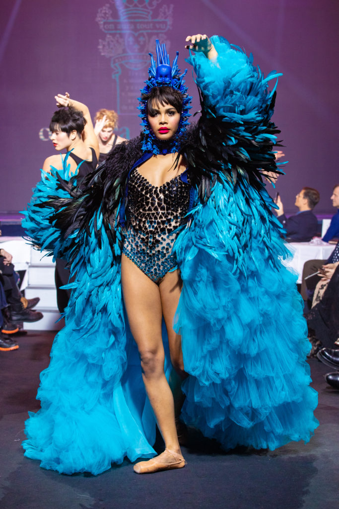 a model wearing  bleu feathers and tull   coat and crystal body and belt  by on aura tout vu haute couture spring summer 2020