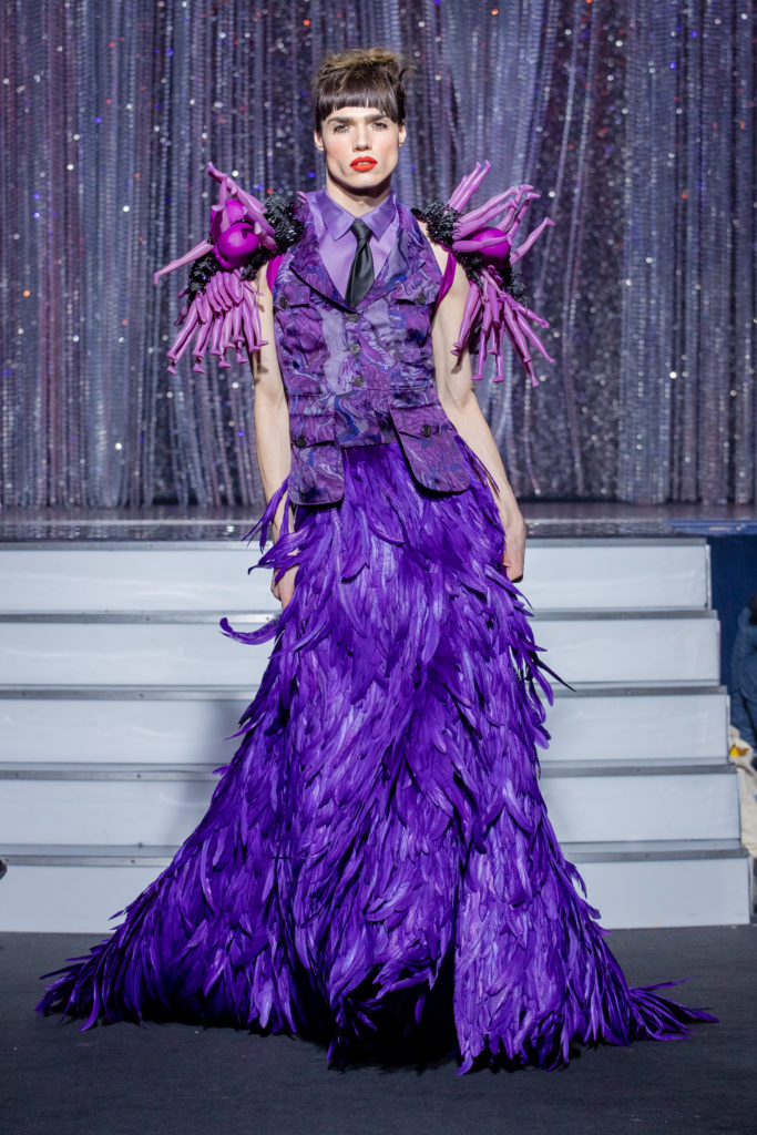 a men model wearing  purpple silk  and feathers outfit  crystal  by on aura tout vu haute couture spring summer 2020