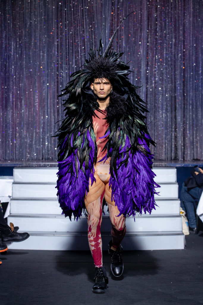 a men model wearing  purpple feathers outfit  crystal   by on aura tout vu haute couture spring summer 2020