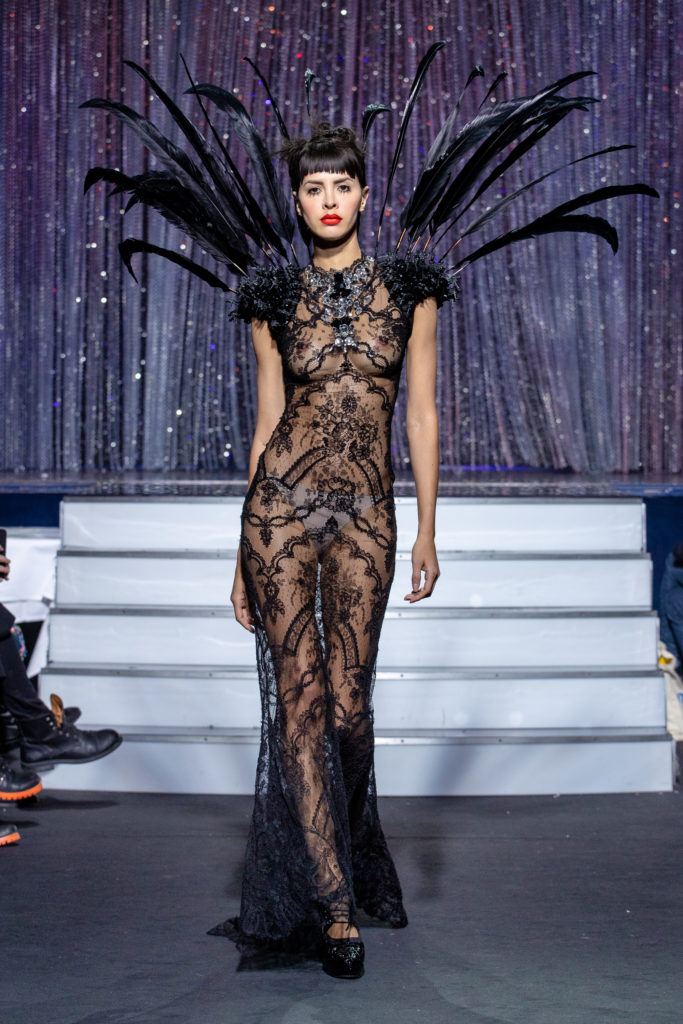 a model wearing  black lace dress  crystal  and feathers by on aura tout vu haute couture spring summer 2020