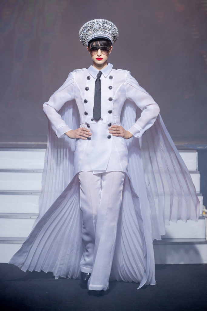 a model wearing Military white outfit pockets and crystal hat eyewear by on aura tout vu couture spring summer 2020