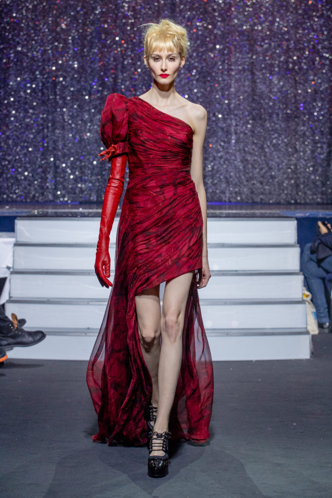 a model wearing  red silk  dress crystal   by on aura tout vu haute couture spring summer 2020