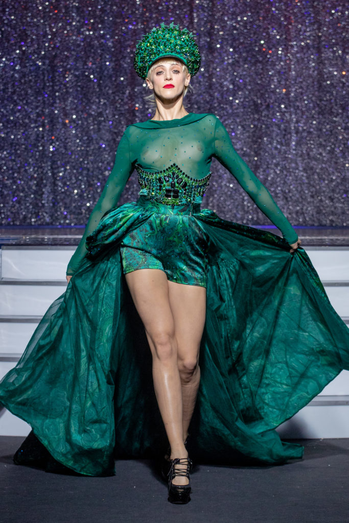 a model wearing  green  silk  outfit  crystal  and belt  and hat by on aura tout vu haute couture spring summer 2020