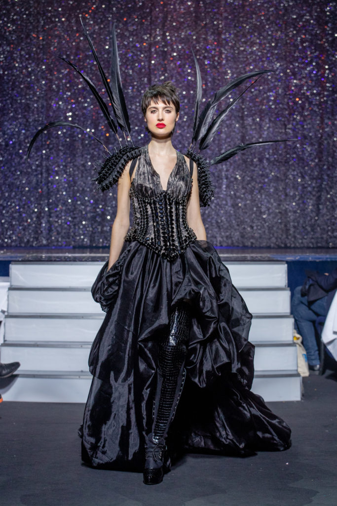 a model wearing  black silk  outfit  crystal  and belt  by on aura tout vu haute couture spring summer 2020