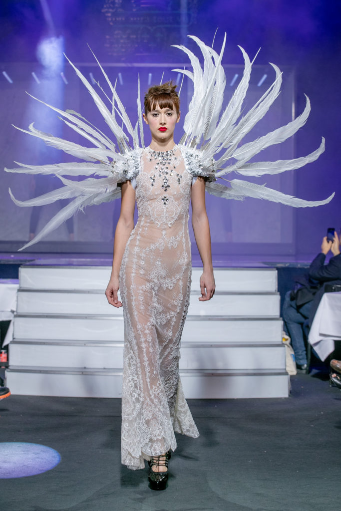 a model wearing  white silk  wedding dress  crystal  and white feathers  by on aura tout vu haute couture spring summer 2020