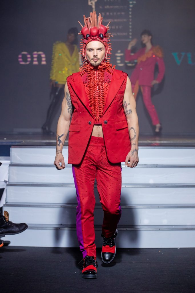 a men model wearing  red and violet silk  outfit  crystal  hat   by on aura tout vu haute couture spring summer 2020